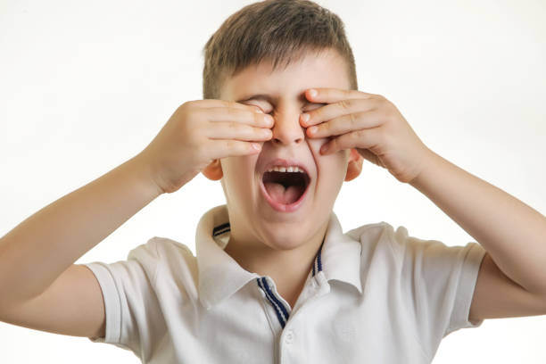 Studio shot of young boy with eye pain. Can not see you concept. stock photo