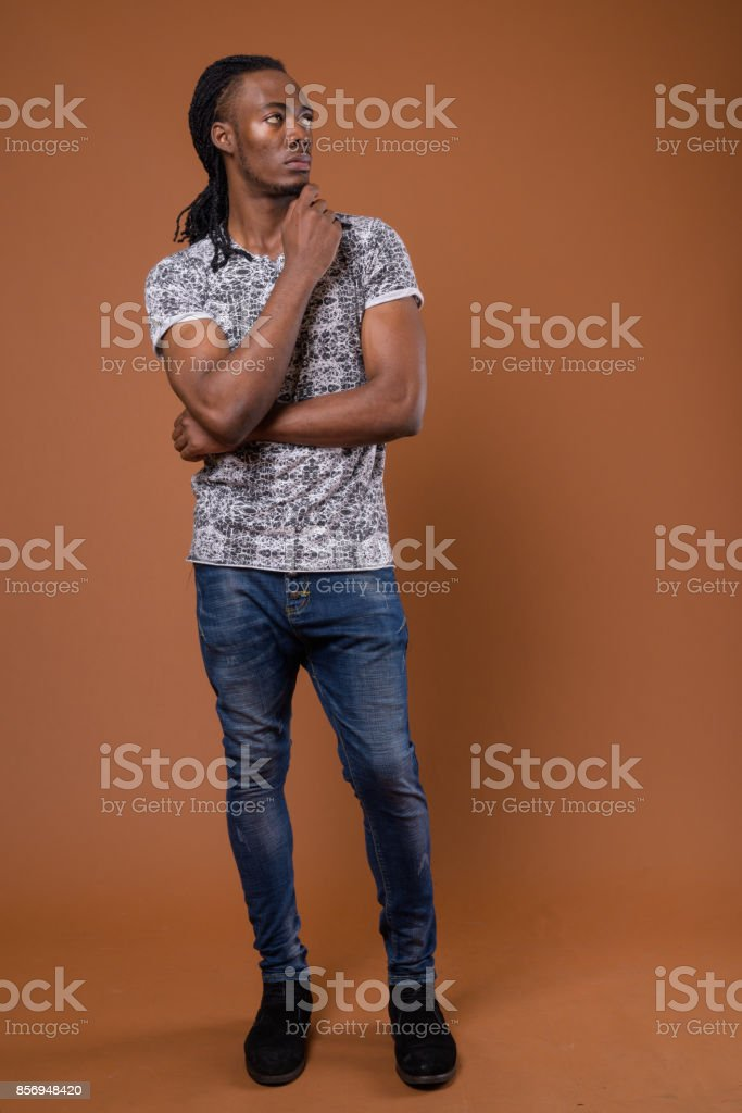 61497415405db Studio Shot Of Young Handsome African Man Wearing Gray Shirt Against ...