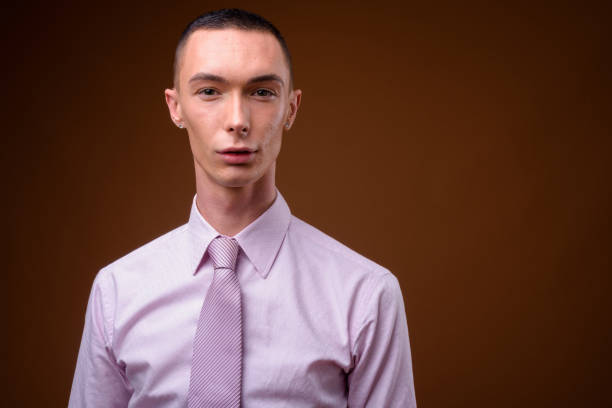 Studio shot of young handsome androgynous businessman wearing pink stylish clothes against colored background stock photo