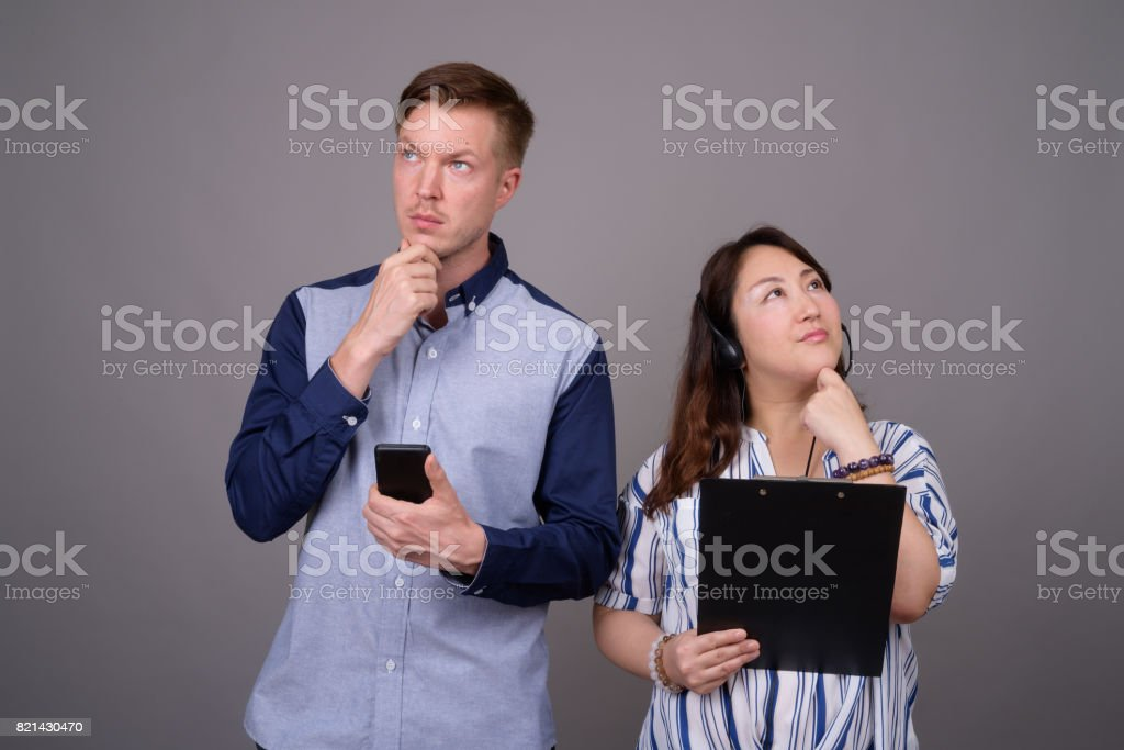 Studio shot of young handsome businessman and mature Asian businesswoman against gray background stock photo