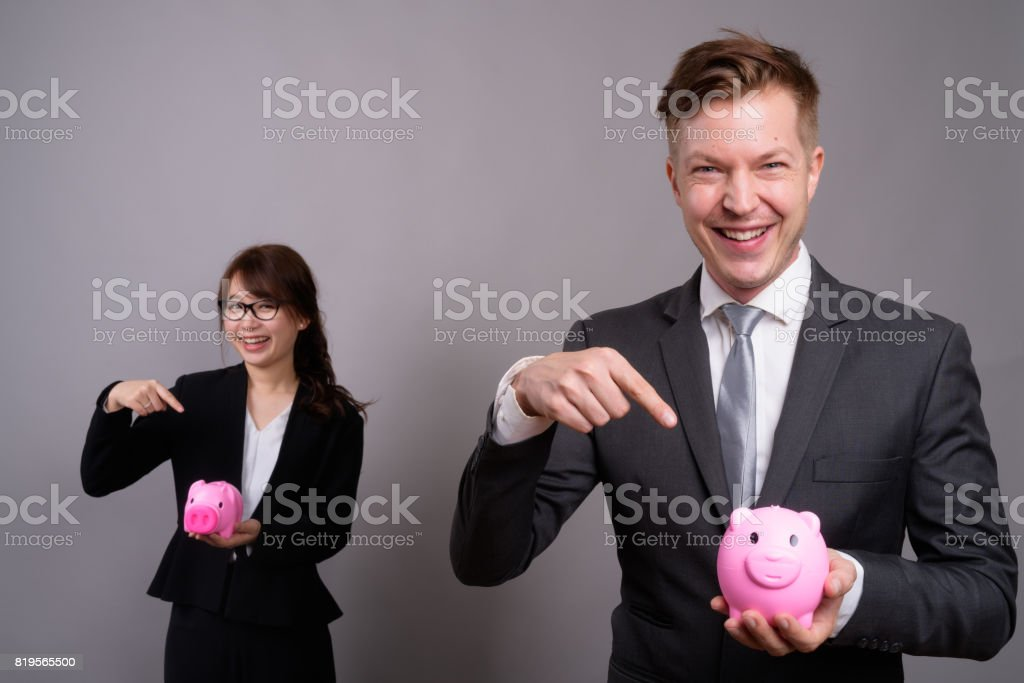 Studio shot of young handsome businessman and young beautiful Asian businesswoman against gray background stock photo