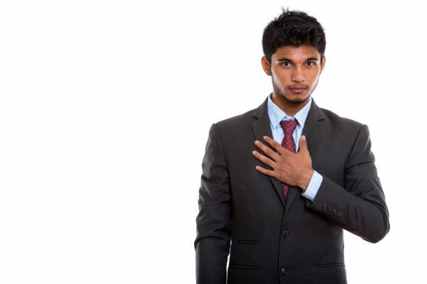 studio shot of young handsome indian businessman with hand on chest - mão no peito imagens e fotografias de stock