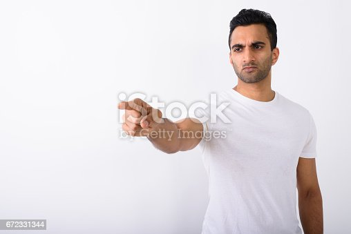 Studio shot of young handsome Indian man against white background horizontal shot