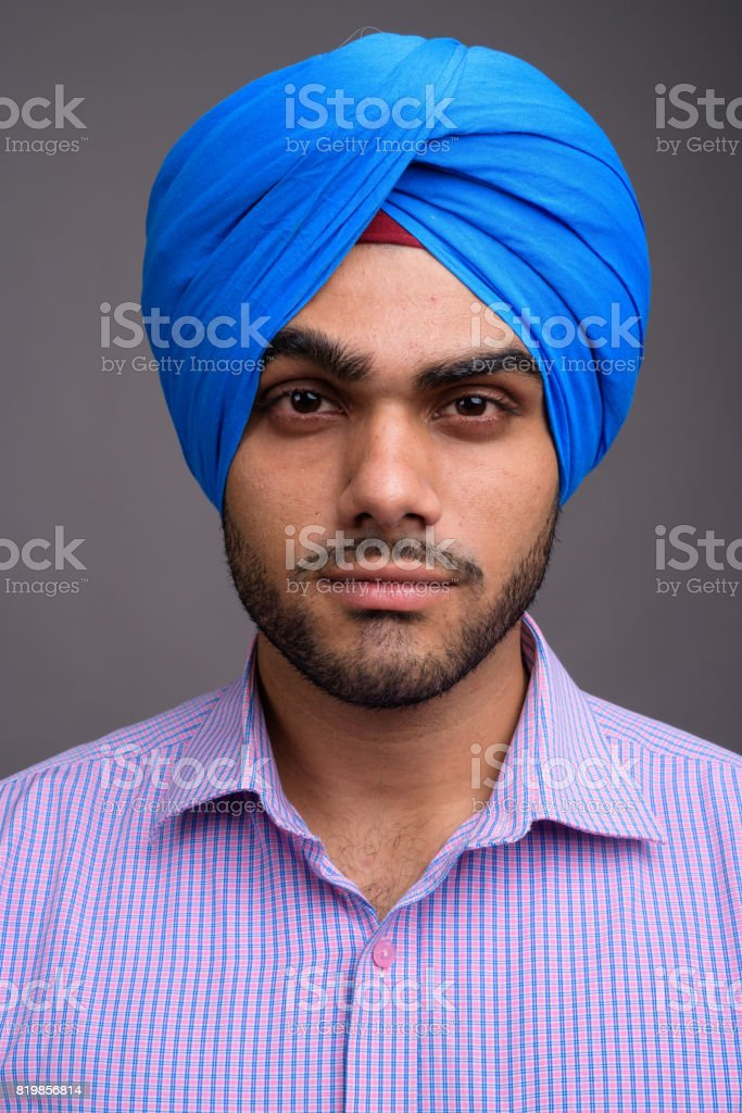 Studio shot of young handsome Indian man wearing turban against gray background stock photo