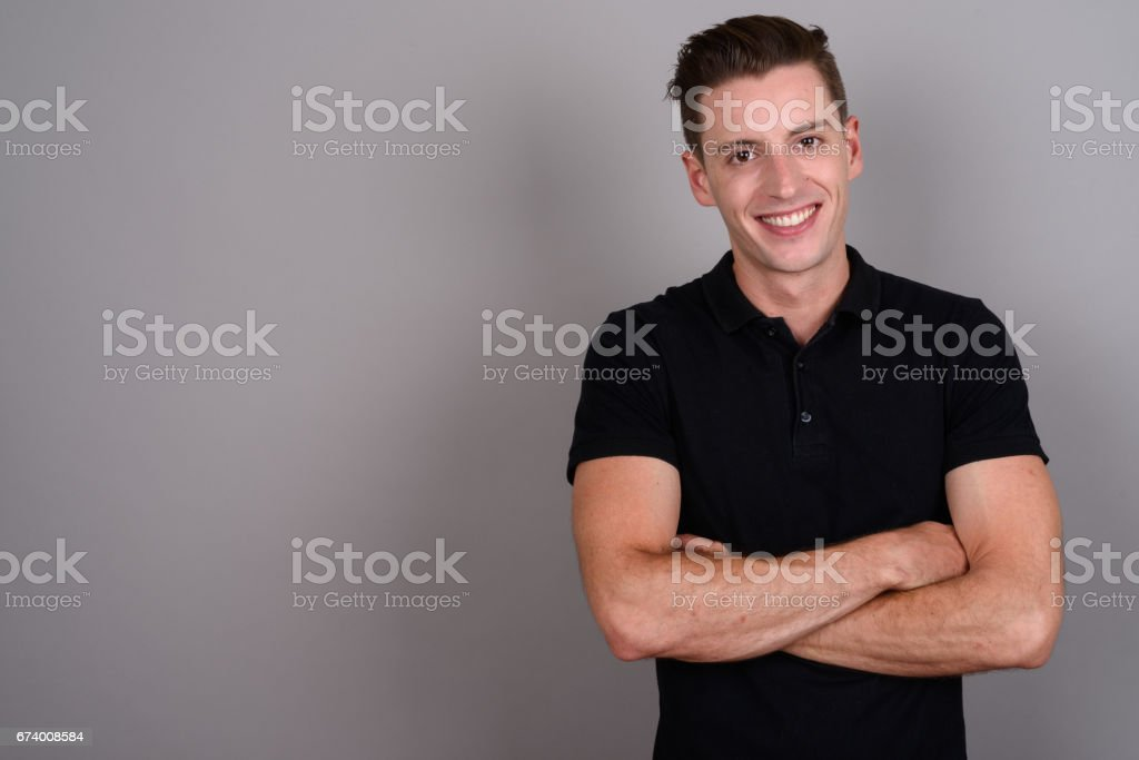 Studio shot of young handsome man against gray background stock photo