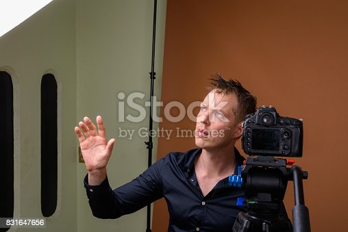 Studio shot of young handsome man photographer checking equipment in wet clothes against colored background horizontal shot