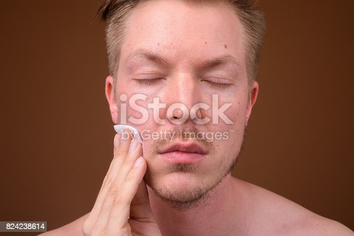 Studio shot of young handsome man shirtless while grooming against colored background horizontal shot