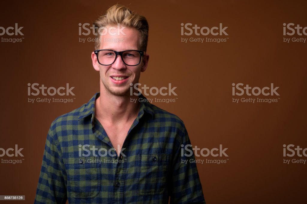 Studio shot of young handsome man wearing smart casual clothing against colored background stock photo