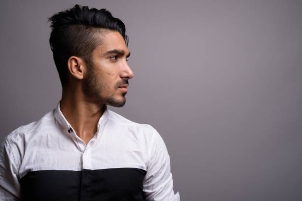 Studio shot of young handsome Persian businessman against gray background stock photo