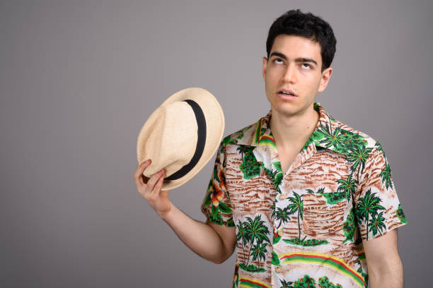Studio shot of young handsome tourist man against gray background Studio shot of young handsome tourist man against gray background horizontal shot rolling eyes stock pictures, royalty-free photos & images