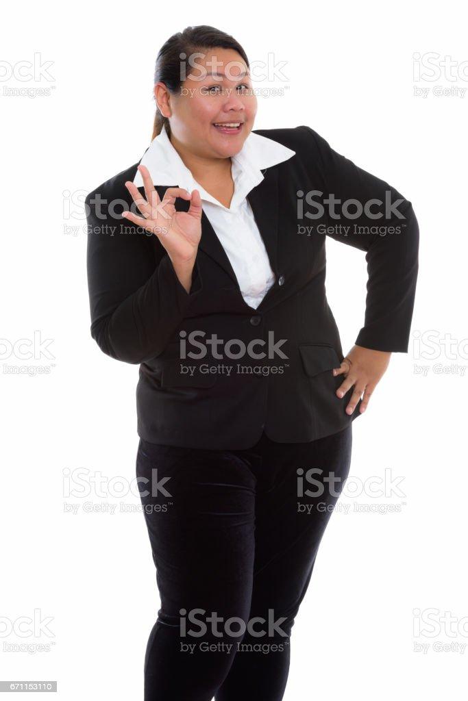 工作室拍攝的年輕快樂胖亞洲女商人微笑著站在同時 ok 的手勢圖像檔