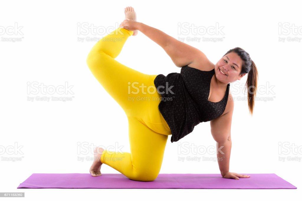 工作室拍攝的年輕快樂胖亞洲女人微笑著,抬起一條腿做瑜伽姿勢時圖像檔