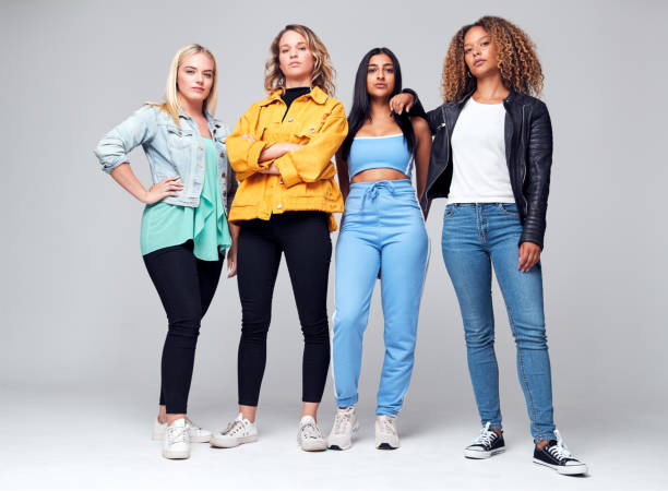 studio shot of young independent multi-cultural female friends looking into camera - battle of the sexes concept stock pictures, royalty-free photos & images