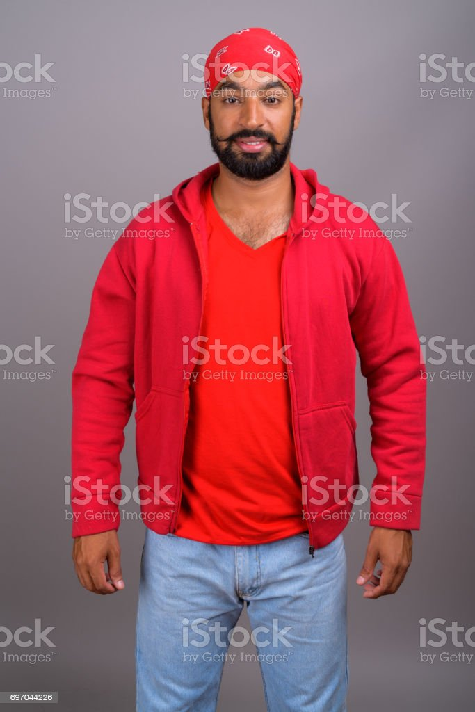 Studio shot of young Indian man wearing red shirt with matching red Bandanna against gray background - foto stock