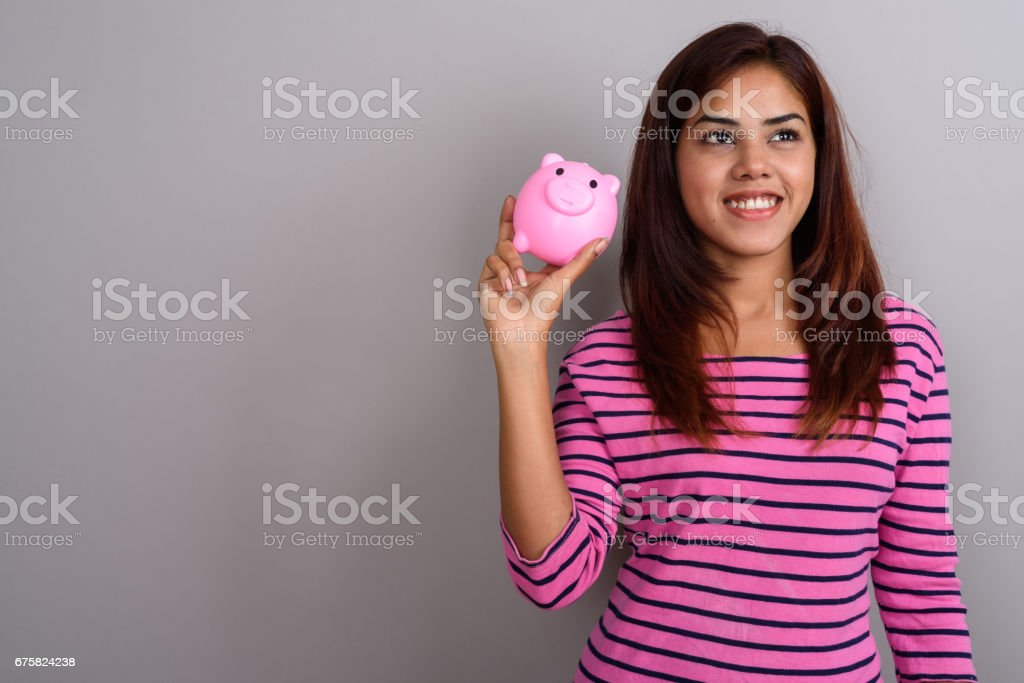Studio shot of young Indian woman against gray background stock photo