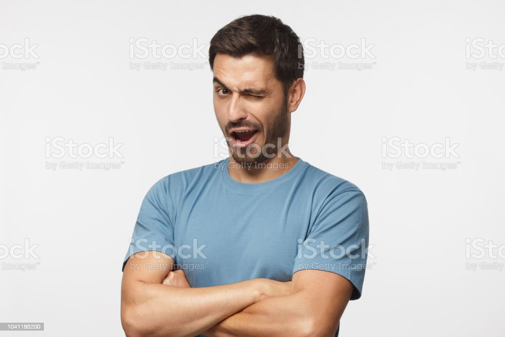 Studio shot of young man winking while flirting, isolated on gray background stock photo
