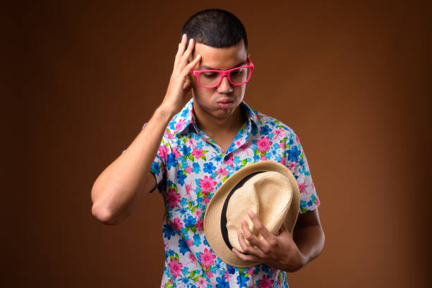Studio shot of young multi-ethnic Asian tourist man against colored background stock photo