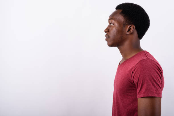 studio shot of young muscular african man against white background - profile view stock photos and pictures