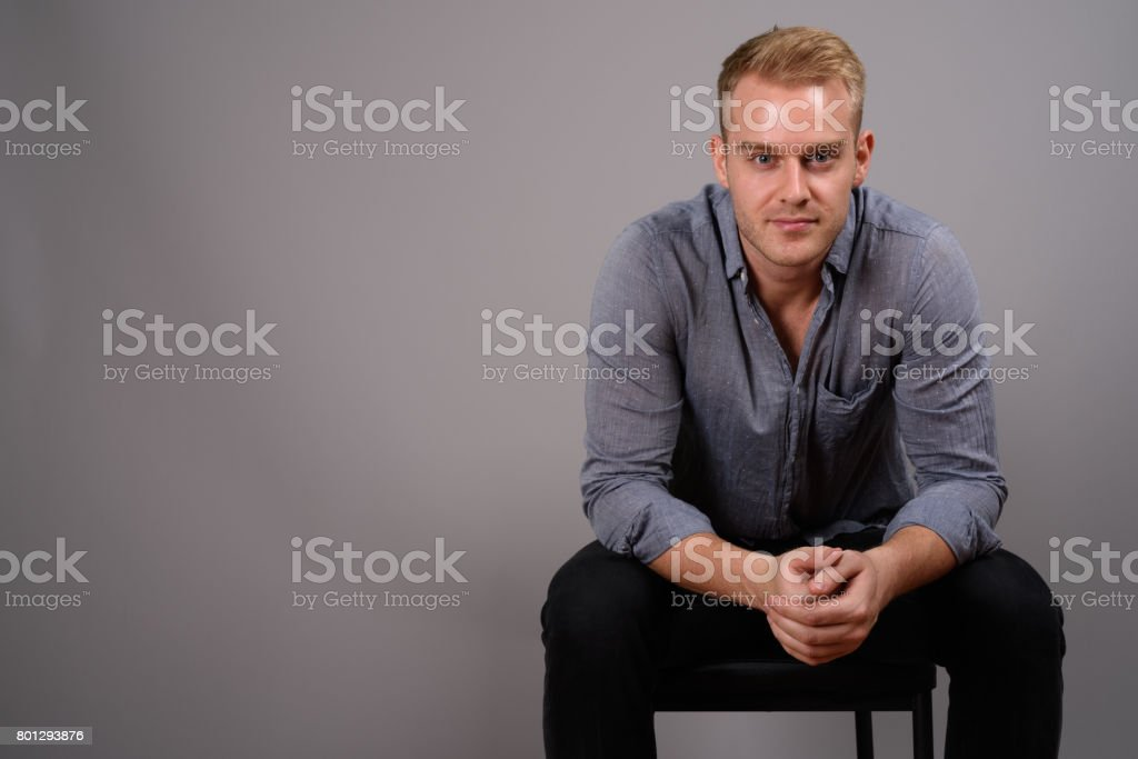 Studio shot of young muscular handsome businessman against gray background stock photo
