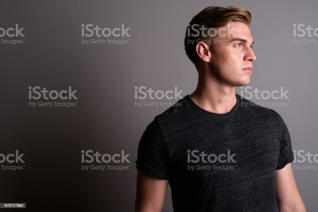 Studio shot of young muscular handsome man against gray background - foto stock