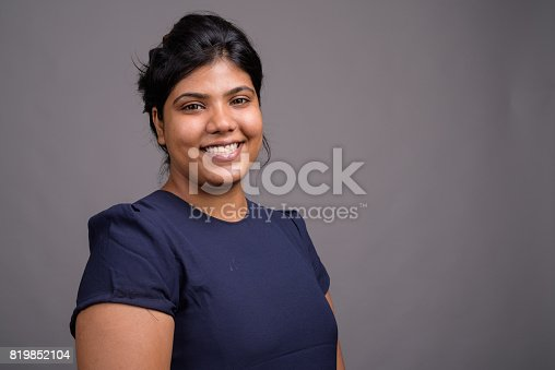 istock Studio shot of young fat beautiful Indian woman against gray background 819852104
