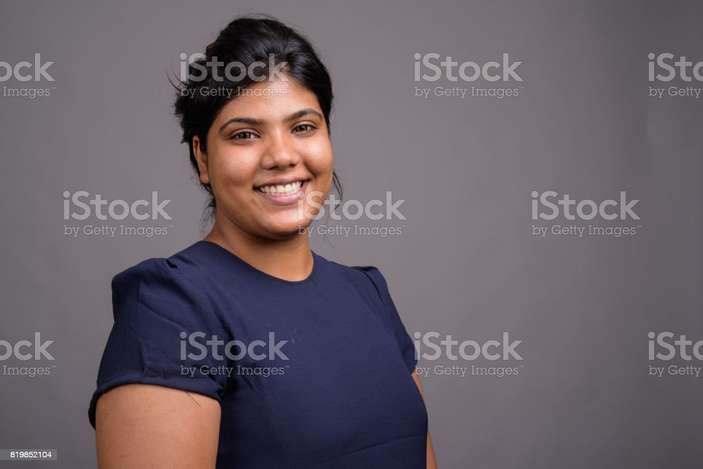 Studio shot of young fat beautiful Indian woman against gray background stock photo