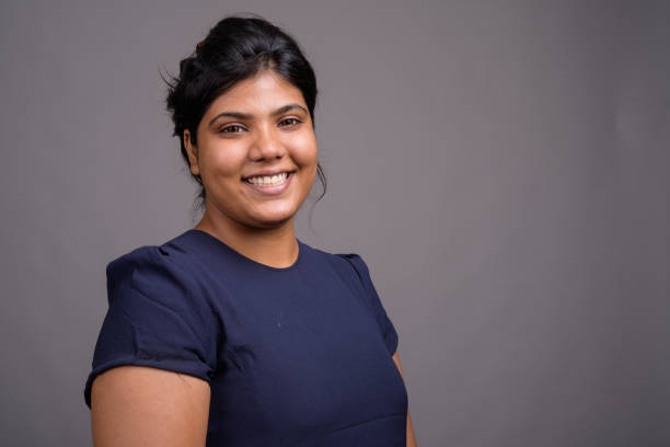 studio shot of young overweight beautiful indian woman against gray background - popolazione indiana foto e immagini stock