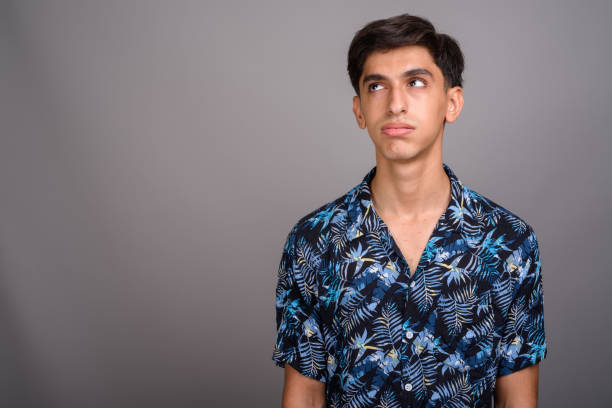 Studio shot of young Persian teenage boy wearing Hawaiian shirt against gray background Studio shot of young Persian teenage boy wearing Hawaiian shirt against gray background horizontal shot rolling eyes stock pictures, royalty-free photos & images