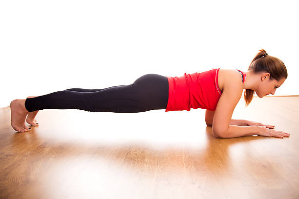 Studio shot of young woman doing plank exercise stock photo