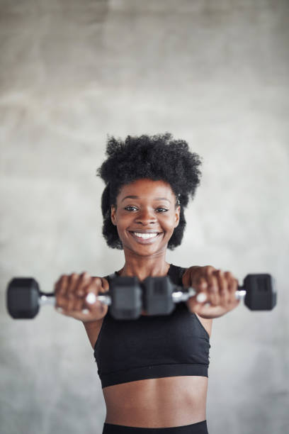 Studio shot of young woman that stands in front of grey background with dumbbells in hands stock photo