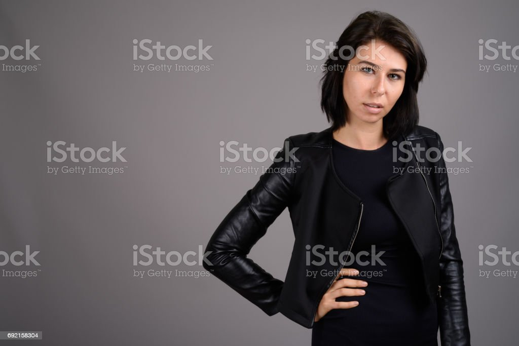 6d7a2d85c5c Studio Shot Of Young Woman Wearing Black Dress With Leather Jacket ...