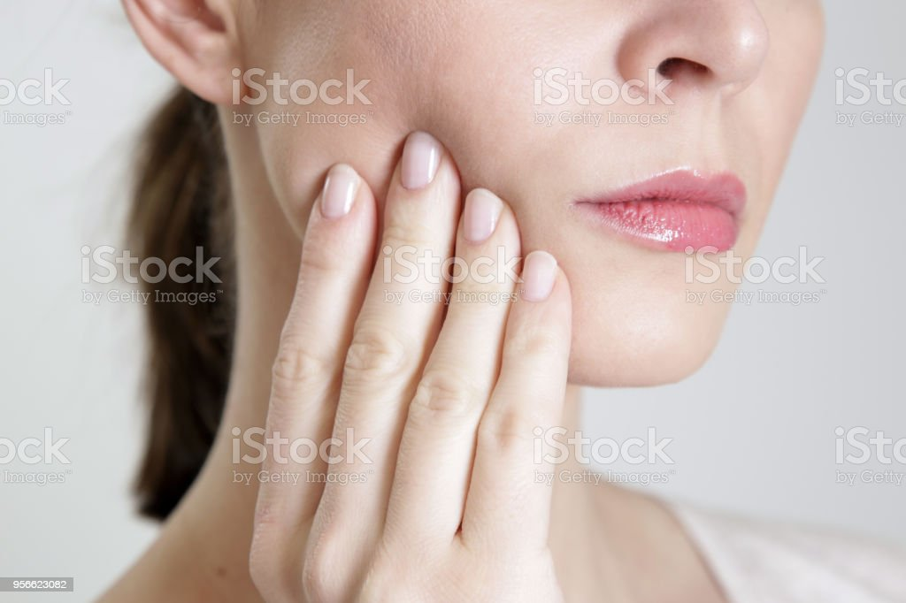 Studio shot of young woman with tooth pain, close up stock photo