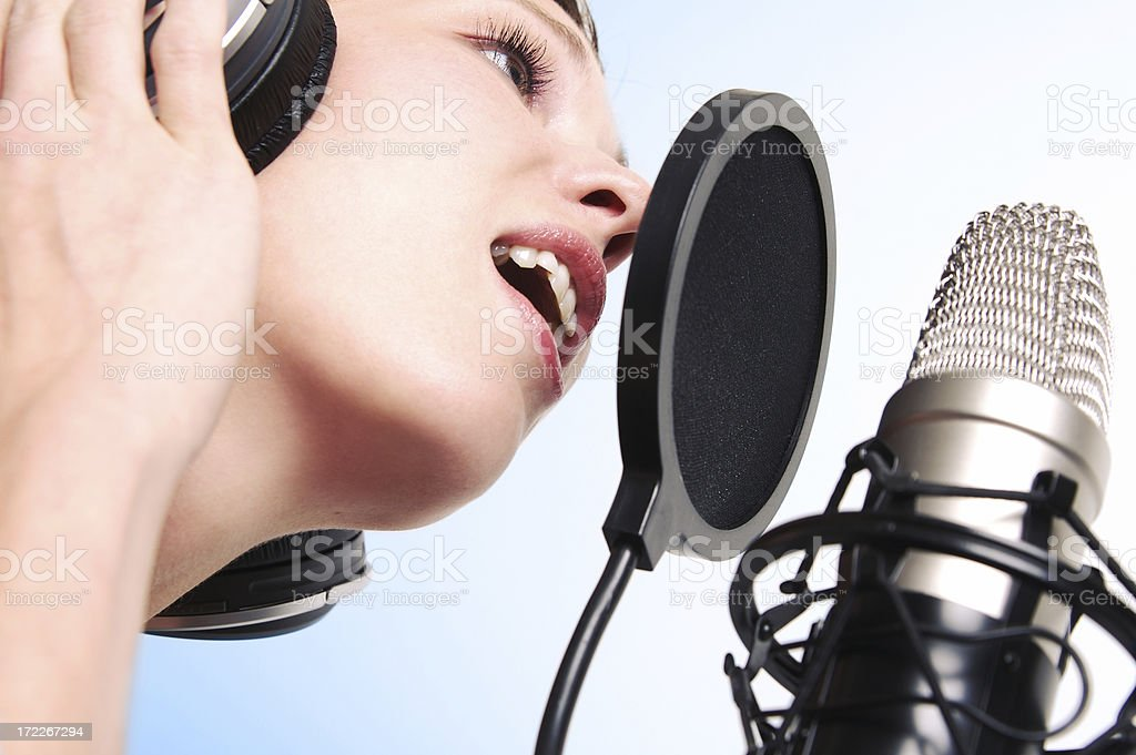 Woman laying down some vocal tracks in a recording studio.