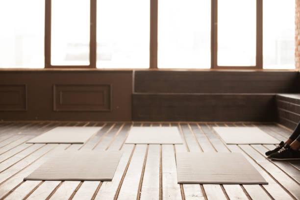 studio mit yoga-matten auf holzboden für gruppentraining - meditationsräume stock-fotos und bilder