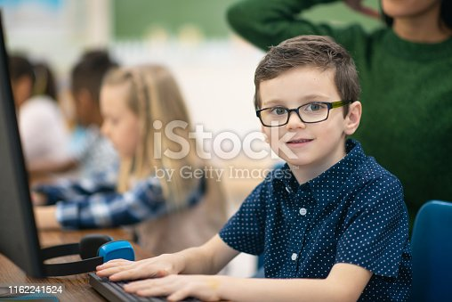 A studious Caucasian boy sits at a computer in his computer lab one day. He is looking right into the camera as his hands rest on his keyboard. Students around him are also typing.