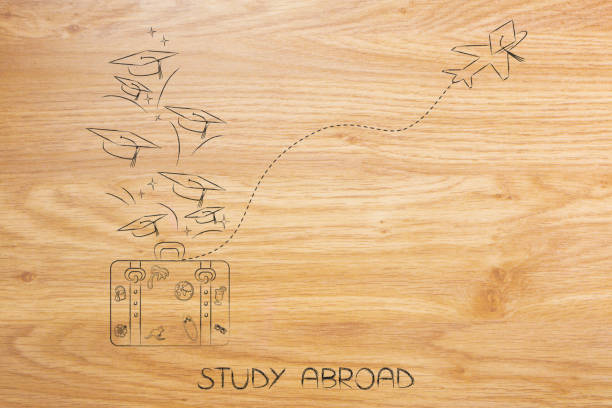 study abroad luggage and airplane with graduation hats stock photo