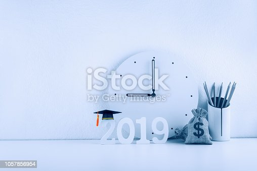 istock 2019 study abroad program, expense and time schedule arrangement, education concept : Black graduation cap on year 2019 wood cut, us dollar money bag, pencils in a storage box, white plain clock at 9 1057856954