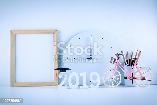istock 2019 study abroad program, time schedule arrangement, education concept : Black graduation cap on year 2019, wood photo frame, pencils, white clock at 9 o'clock on student desk table. Light blue theme 1057856882