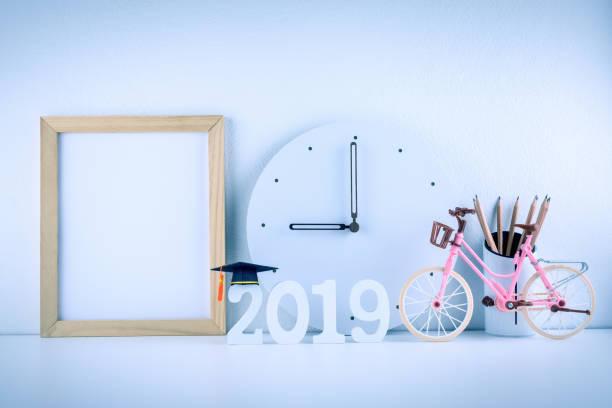 2019 studieren im Ausland-Programm, Zeit Zeitplan Anordnung, Bildungskonzept: Graduation Cap im Jahr 2019, Holz Bilderrahmen, Bleistifte, weiße Uhr an 09:00 auf Schüler Schreibtisch Tisch schwarz. Helle blaue Design – Foto