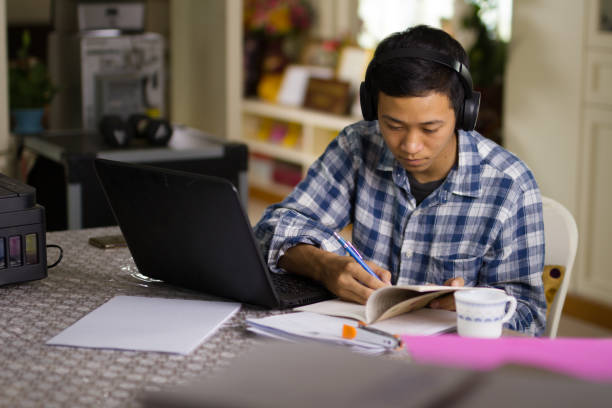 Study at home using laptop and wear headset stock photo
