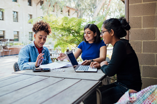 A shot of a group of students laughing and talking while studying outside at a university in Perth, Australia.