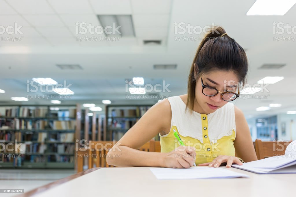 study education, woman writing on a paper, working women stock photo