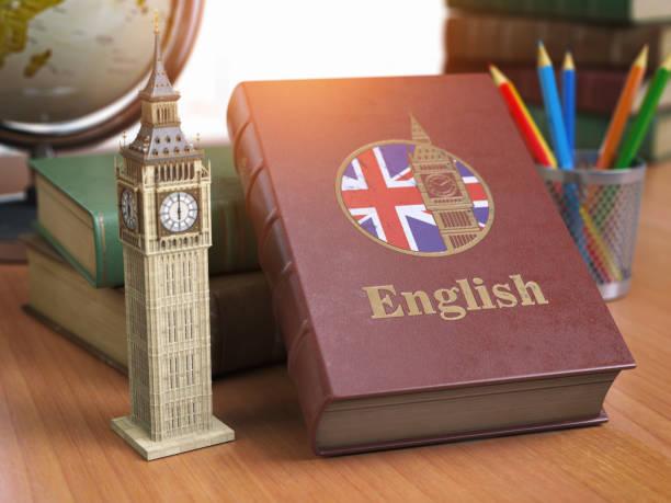 étudier et apprendre le concept anglais. réservez avec le drapeau de la grande-bretagne et big ben tour sur la table. - langue anglaise photos et images de collection