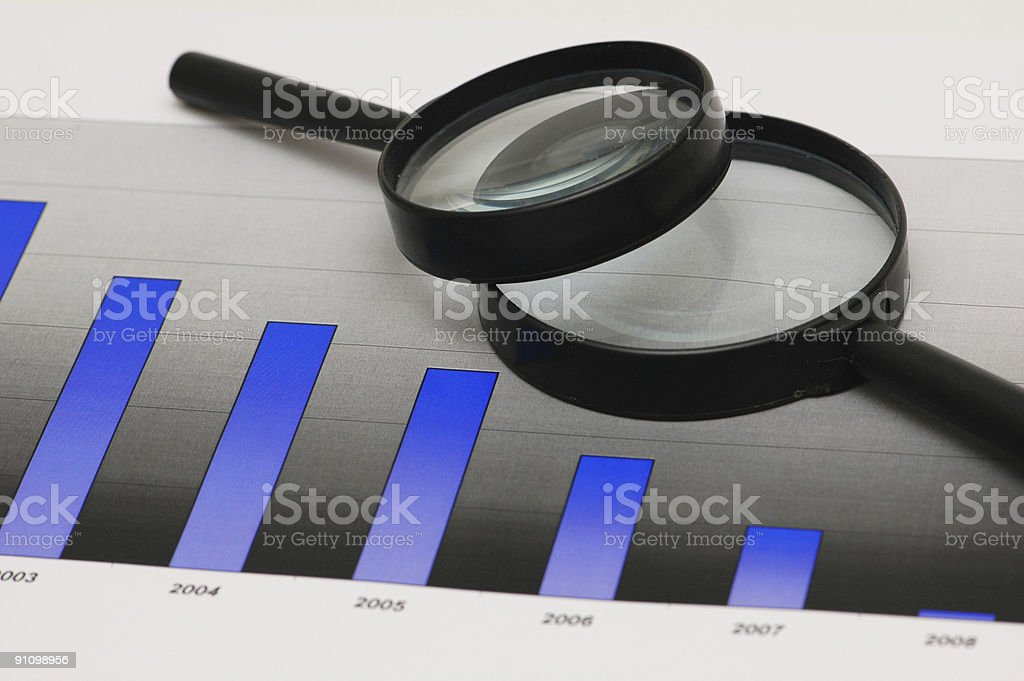 Studying business opportunities - magnifying glasses over the bar charts royalty-free stock photo