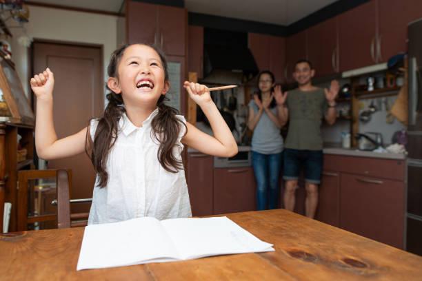 後ろから見守る少女、母、父の勉強 - 小学生勉強 ストックフォトと画像