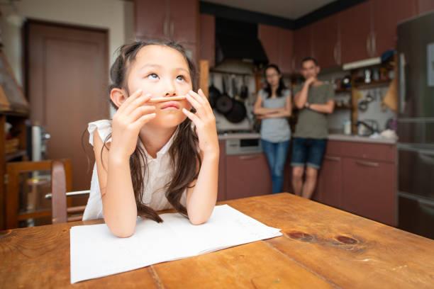 後ろから見守る少女、母、父の勉強 - 小学校 ストックフォトと画像