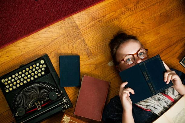 akademisches lernen mädchen auf dem boden mit büchern und schreibmaschine - kurzgeschichten stock-fotos und bilder