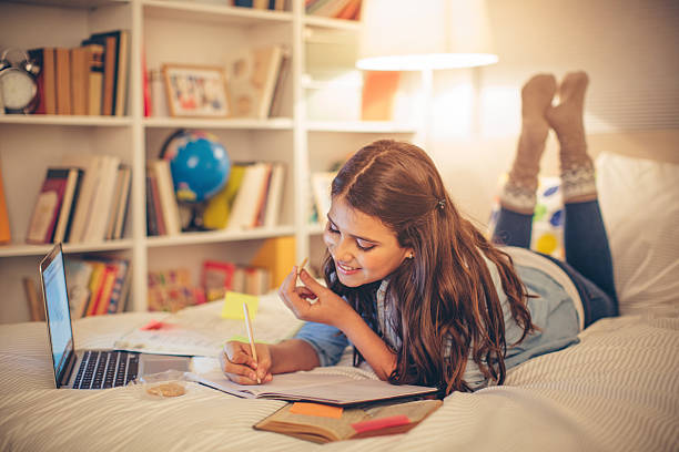 Studying time! Teenage girl lying on bed in her room and studying. She is using computer to help her for researching. Eating cookie for snack. Evening or night with beautiful yellow lights lightning the scenes. girl bedroom stock pictures, royalty-free photos & images