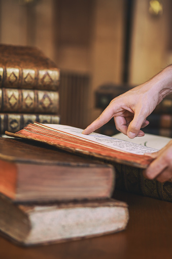 Hands holding ancient book on a desk in library's reading room. Stacks of books in the background. Pointing finger.