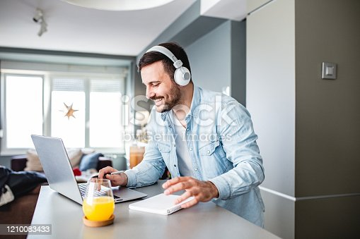 Young man is at home, with headphones and he is studying with laptop